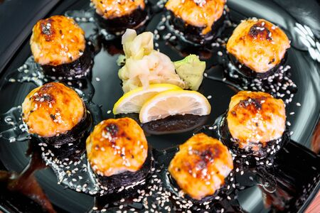 photo of baked Japanese rolls in a black plate Фото со стока