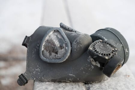old rubber gas mask on the street in winter