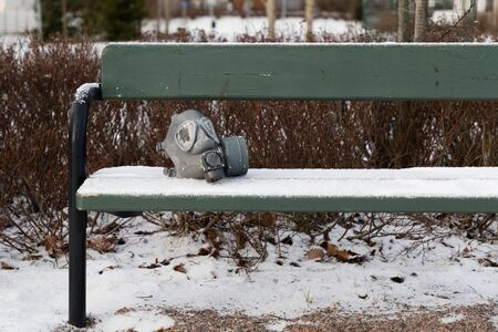 old rubber gas mask on a park bench in winter