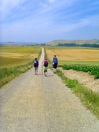 Three people walking down a dirt country road.