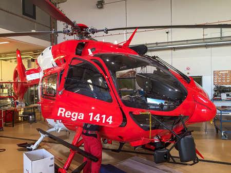 Zurich, Switzerland - November 11, 2018: Swiss Rega air ambulance and rescue helicopter in service hangar at Zurich International Airport Publikacyjne