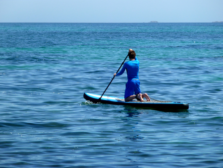 young man practicing paddle on the beach with calm sea