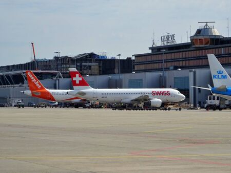 Passenger planes parked on the runway of Geneva Airport, Switzerland. Passenger traffic in summer.