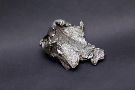 Meteorito Tektite Sikhote Alin aislado sobre fondo gris Foto de archivo