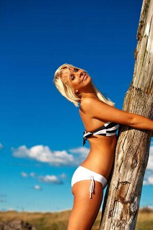 Girl in tube bikini hugging a tree by a blue-sky beach Stock Photo - 6335181