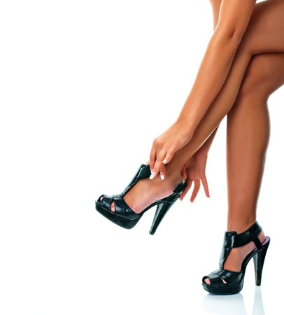 Woman with nicely tanned legs putting on high heel shoes to go to a party photo