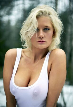 wet breast: Portrait of a gorgeous blonde in wet white tanktop in the forest. Stock Photo
