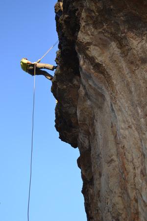 Girl descending on the rope along the rocks. Stock Photo