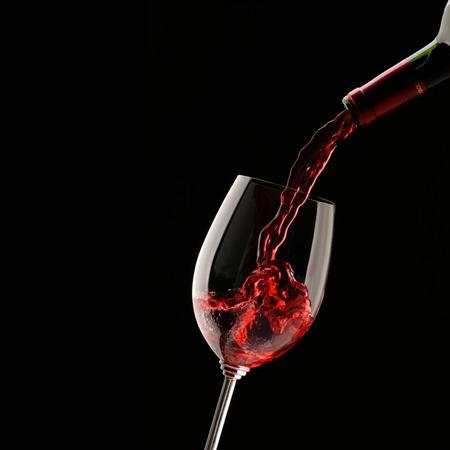 Het gieten van rode wijn in glas op een zwarte achtergrond Stockfoto