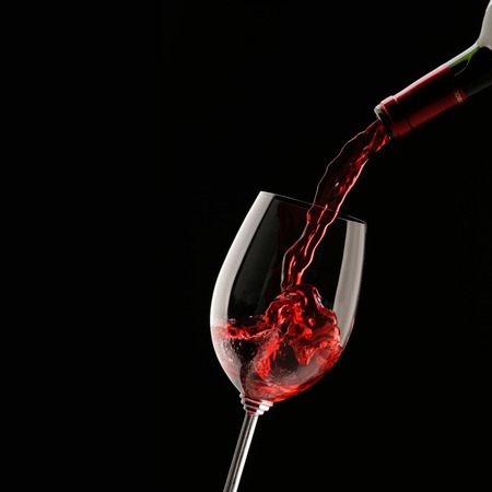 Pouring red wine into wine glass on a black background Standard-Bild