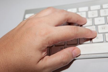 inputting: Hand touching middle of gray metallic computer keyboard with fingertips Stock Photo