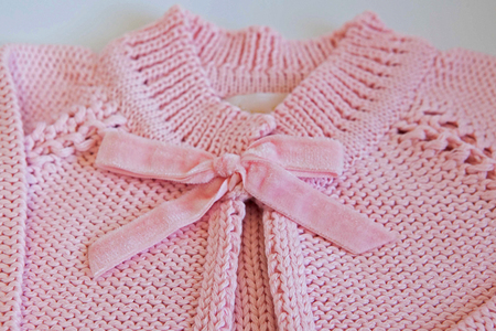 tricot: Closeup on pink baby blouse made of tricot with delicated bow
