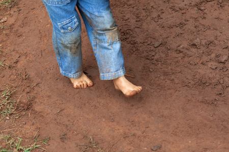 dirty feet: Kid wearing jeans trousers walking on muddy ground