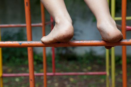 Toddler climbs playground with mud dirty feet Stock Photo