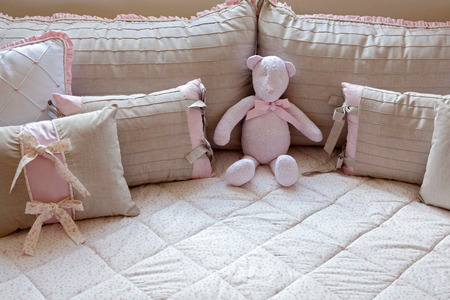 natual: Pink ted bear and pillows in girl bed with natual light