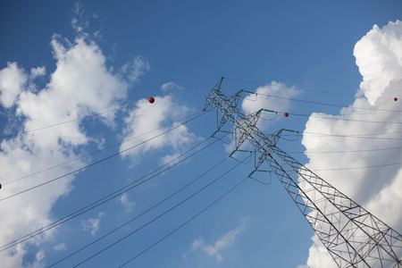 farther: Farther diagonal powerline with blue sky and clouds Stock Photo