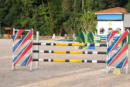 Horse jumping obstacles and sticks in sandy terrain