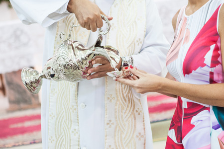 Priest pouring holy water into pot in womans hand
