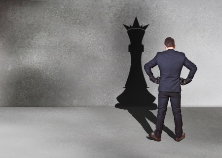 businessman with chess king shadow for street photo