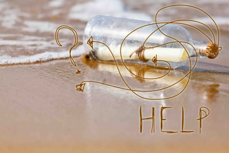 news update: help message in a bottle on a sand and water background Stock Photo