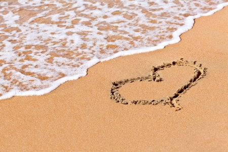 anniversary beach: heart in the sand in a holiday beach Stock Photo