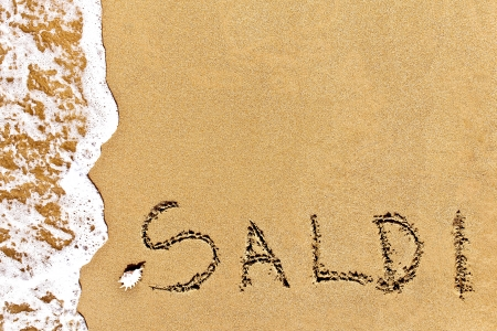 written saldi drawn on the sand on a beach with shell