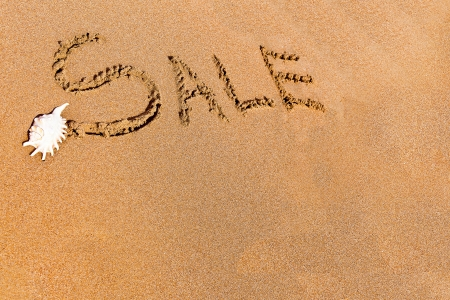 written sale drawn on the sand on the beach Stock Photo - 20212578