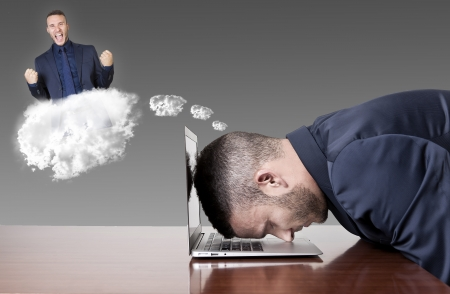 businessman dreaming success with head on laptop Stock Photo
