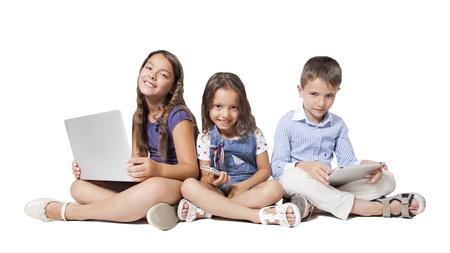 učit se: děti s novou technologií, izolovaných na bílém pozadí Reklamní fotografie