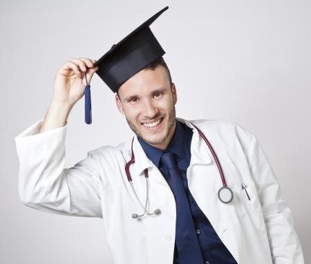 medicamentos: joven m�dico sonriendo con birrete sobre un fondo blanco Foto de archivo