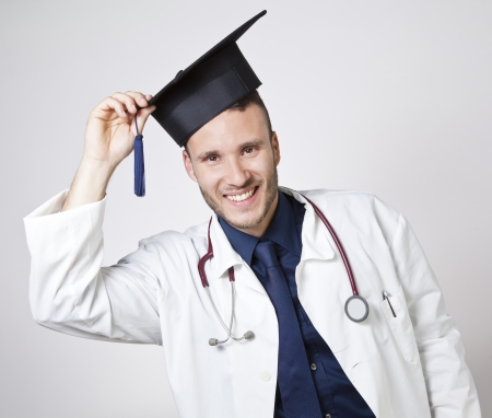 young doctor smiling with mortarboard on a white background