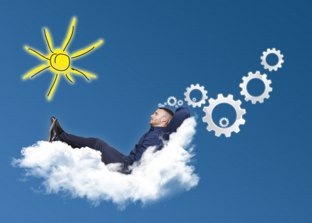 businessman on cloud with white cogs on a blue background photo