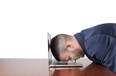 Stressed businessman sleep with head on laptop photo