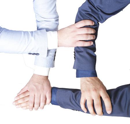 manos unidas: cuatro manos al trabajo en equipo aislado en un blanco