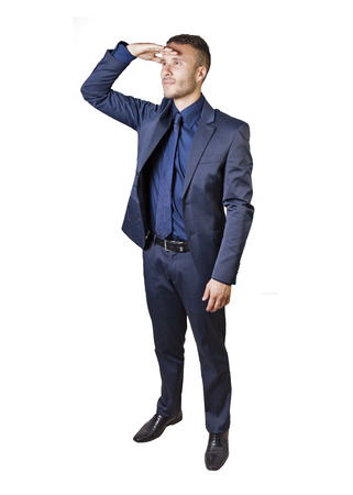 a young businessman with hand to forehead to scan the horizon photo