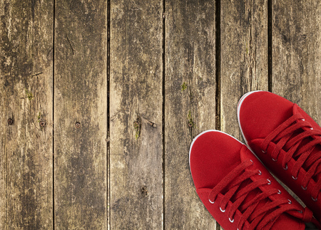 wooden shoes: red sneakers in the right side on wooden deck  Stock Photo