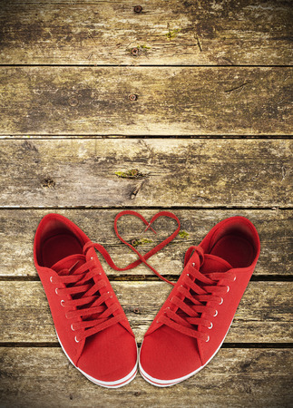 Heart-shaped red shoelaces of sneakers on wooden deck photo