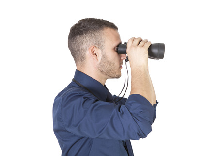 a young businessman with binoculars isolated on a white background photo