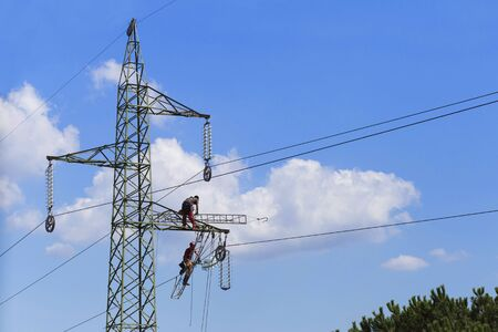 electricity pylon: two men working on a trellis in a blue sky Stock Photo