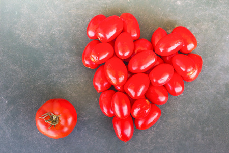 lycopene: red organic juicy tomatoes heart on gray background Stock Photo