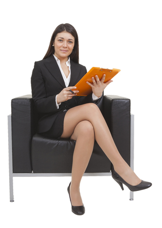tailleur: Businesswoman sitting on black armchair looking documents