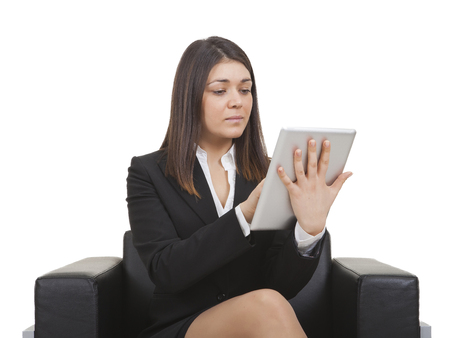 tailleur: Businesswoman sitting on black armchair looking tablet Stock Photo