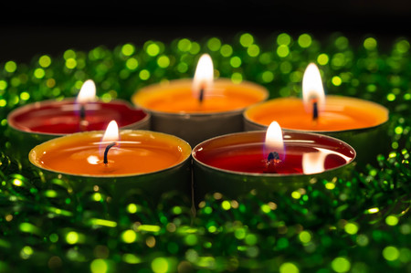 Burning candles and green sparkling decor photo