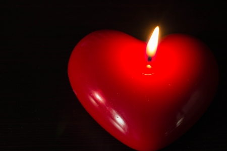 Red candle in the form of heart photo