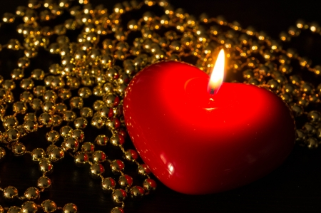 Red candle in the form of heart with a gold beads photo