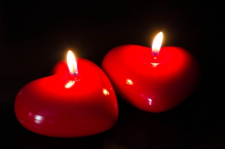 Two red candles in the form of heart photo
