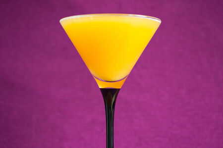 bar ware: Orange juice in a martini glass on a violet background Stock Photo