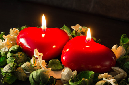 Couple of red candles among the dried flowers photo