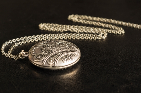 Pendent from metal with a chain on a black  Stockfoto