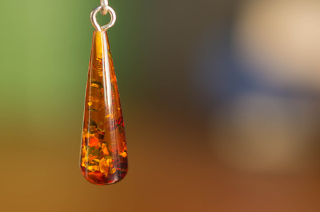 Earring from amber in the form of a cone close up Stock Photo - 24462910